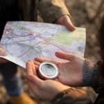 close up travelers with map compass scaled