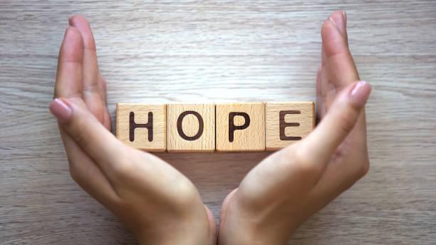 Hope written on blocks stuck between 2 hands